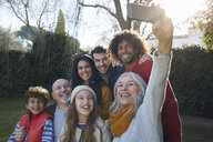 Multi generation family huddled together using smartphone to take selfie, smiling - CUF17671
