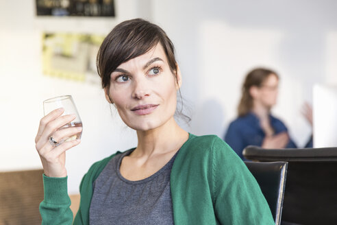 Mature woman in office holding drinking glass looking away - CUF17748