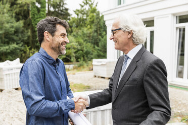 Builder and architect on construction site shaking hands smiling - CUF17805