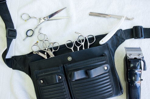 Overhead view of hairdressers tool belt with scissors, hair clippers and straight razor - CUF17859