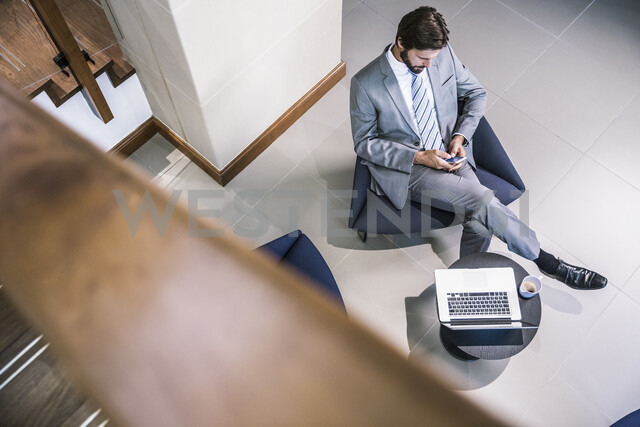 High angle view of businessman in lobby looking down at smartphone - CUF17871