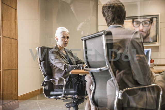 View through glass of businesspeople sitting on office chairs making video call - CUF17883