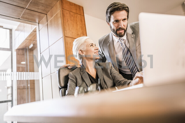 Businesspeople at desk looking at laptop smiling - CUF17889