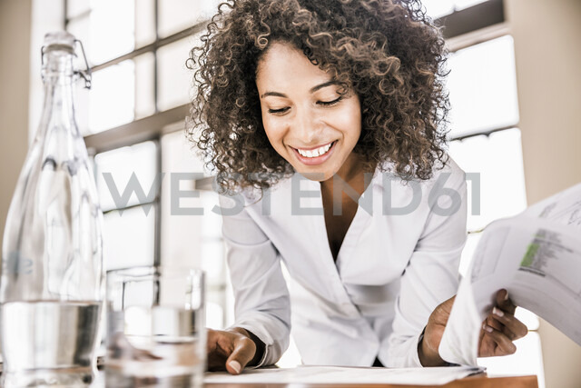 Curly haired business woman looking down at paperwork smiling - CUF17955 - Matelly/Westend61