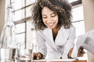 Curly haired business woman looking down at paperwork smiling - CUF17955