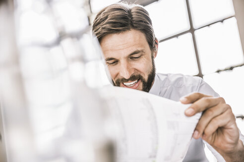 Bearded businessman looking down at paperwork smiling - CUF17958
