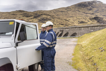 Workers with utility vehicle by dam at hydroelectric power station - CUF18003