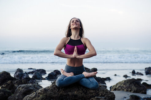 Young woman practicing lotus yoga pose on rocks at beach, Los Angeles, California, USA - ISF06704