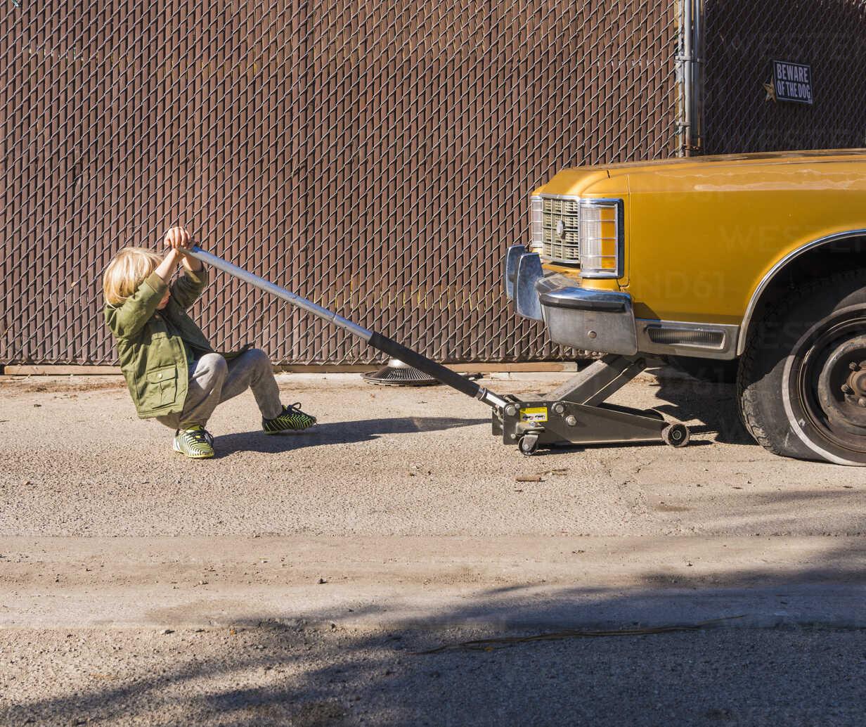 Boy using car jack to raise car - ISF06719 - JLPH/Westend61