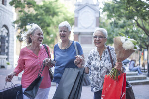 Happy senior and mature women carrying shopping and bouquet in city - ISF06749