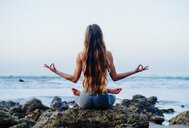 Rear view of young woman with long hair practicing lotus yoga pose on rocks at beach, Los Angeles, California, USA - ISF06788