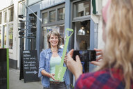 Friend photographing woman in front of shop holding open sign - CUF18062