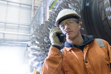 Worker with walkie talkie in front of gas turbine in gas-fired power station - CUF18091