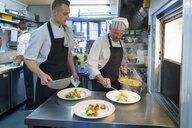 Chefs preparing dishes in traditional Italian restaurant kitchen - CUF18166