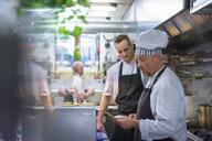 Chefs reading order in traditional Italian restaurant kitchen - CUF18169