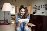 Young woman sitting on dining table reading smartphone texts - CUF18229