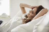 Surface level view of beautiful young woman lying back on bed - CUF18238