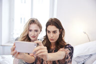 Two young women sitting on bed taking smartphone selfie - CUF18253