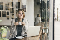 Woman drinking coffee whilst gazing from coffee shop window seat - ISF06825
