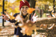Happy young woman wearing red knit hat throwing autumn leaves in park - ISF06861