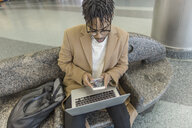 Young businessman sitting in train station using smartphone and laptop - ISF06903
