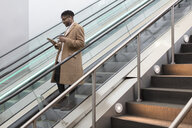 Young businessman moving down train station escalator reading smartphone - ISF06906