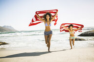 Mother and daughter are running on beach holding towel over head - CUF18288