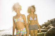 Mother and daughter enjoying sun beside rocks - CUF18297