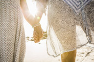 Mother and daughter holding hands on beach - CUF18315