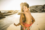 Mother giving son piggyback ride on beach - CUF18348
