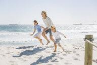 Father and children running on beach - CUF18369