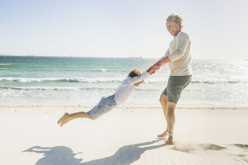 Father swinging son on beach - CUF18381