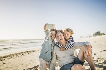 Father and sons taking selfie on beach - CUF18399