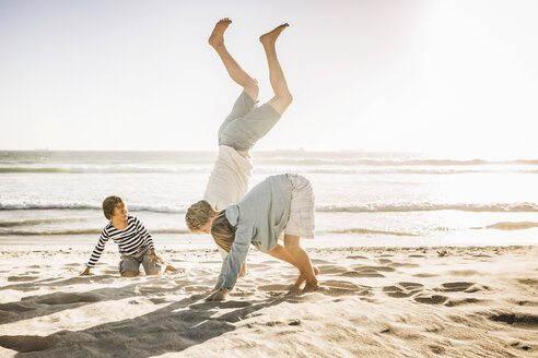 Father and sons doing handstand on beach - CUF18402