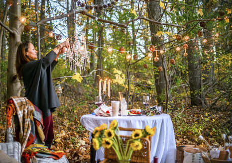 Mature woman hanging decorative lights in woods - ISF07037