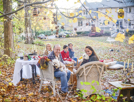 Portrait of mature couple with teenage and adult children picnicing in garden - ISF07043
