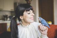Young woman smiling at pet bird indoors - CUF18439