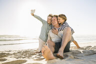 Father and sons at beach using smartphone to take selfie smiling - CUF18574