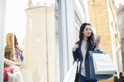 Woman carrying shopping bags looking at smartphone smiling - CUF18664