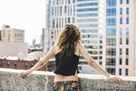 Rear view of woman on rooftop wearing crop top looking away at view, Boston, Massachusetts, USA - ISF07086