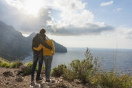 Mid adult couple looking out to sea from cliff top, Majorca, Spain - CUF18763