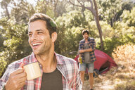 Male camper with coffee in forest, Deer Park, Cape Town, South Africa - CUF18823