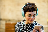 Mid adult woman, wearing headphones, looking at smartphone, smiling - ISF07185