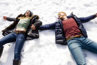 Couple lying down in snow - ISF07224