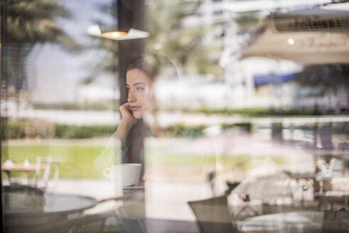 Woman gazing behind reflective cafe window, Dubai, United Arab Emirates - CUF18937