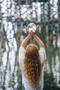 Rear view of woman holding up crystal ball in front of wood river pier - ISF07278