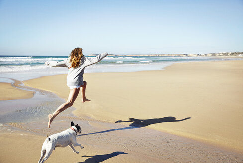 Mature woman and dog leaping over water on beach, Conil de la Frontera, Spain - ISF07320
