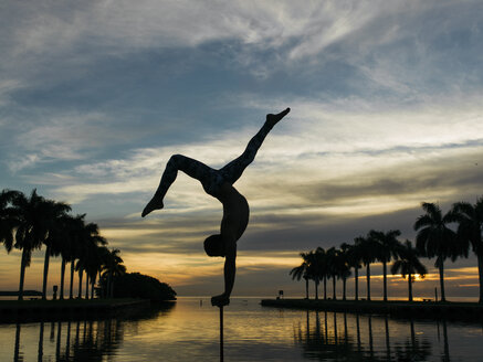 Mature man balancing on pole, dusk, South Pointe Park, South Beach, Miami, Florida, USA - ISF07341