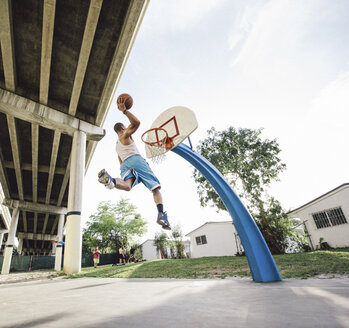 Low angle view of young man in mid air holding basketball jumping for hoop - ISF07347