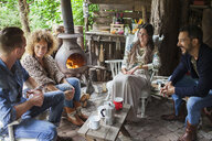 Four adult friends drinking coffee in open cabin with wood stove - ISF07404